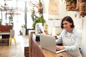 Female Sales Assistant Working On Laptop Behind Sales Desk Of Florists Store