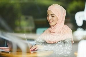 Muslim woman answering e-mails